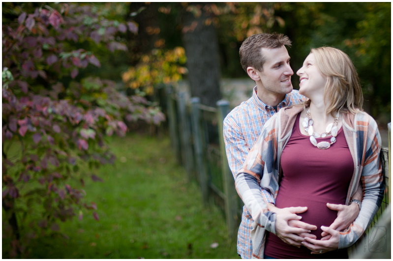 Maternity Photos Taken By Benson Expecting Wife And Husband Embrace Along A Fence In Baltimore Maryland